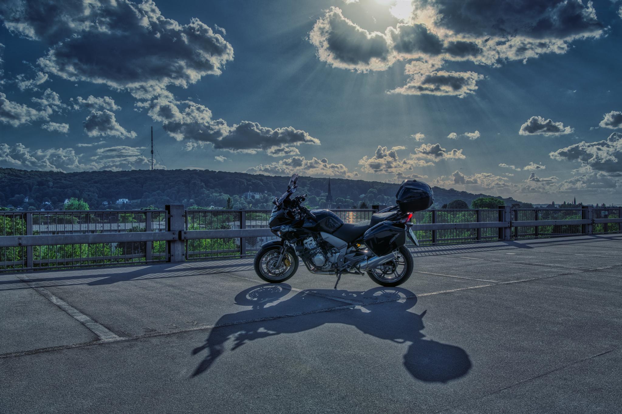 Honda CBF 1000 mit Schattenwurf vor bewölktem Himmel mit Sonnenstrahlen